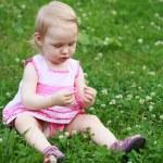 belle petite fille en robe rose est assis sur l'esprit de la pelouse — Photo #27742819