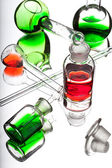 Chemistry laboratory glassware with colour liquids on white back — Stock Photo
