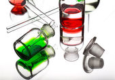Chemistry laboratory glassware with colour liquids white backgro — Stock Photo