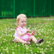 Beautiful little girl is sitting on green lawn with flowering cl — Stock Photo