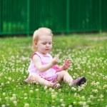 belle petite fille est assise sur la pelouse avec floraison cl — Photo #28132257