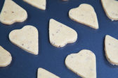 Heart shaped raw dough cookies with caraway on metal baking tray — Stock Photo