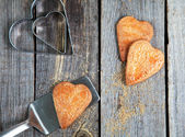 Golden Heart shaped cookies with a sugar crust on wooden table — Stock Photo