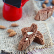 Chocolate biscotti with almonds and red coffee pot on a wooden t — Stock Photo