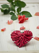 A red heart in front of a red rose — Stock Photo