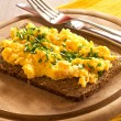 Scrambled eggs with chives on a slice of wholemeal bread — Stock Photo #22824598