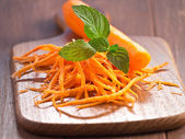 Julienne de carottes avec un jus de carotte sur un plateau en bois — Foto de Stock