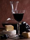 Ett glas rött vin med ost och vindruvor — Stockfoto