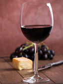 A glass of red wine with cheese and grapes — 图库照片