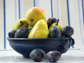 Fruit bowl with plums and pears — Photo