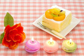 Artificial rose and fruit cake and candles — Stock Photo
