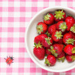 Strawberries in a bowl and ladybird — Stock Photo #23972381