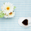 Coffee and white artificial flowers - Stock Photo