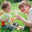 Smiling mother and son sitting on a field of flowers — Stock Photo