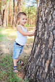 Beautiful boy stands near a tree in the forest — Stock Photo