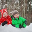 Stock Photo: Beautiful boy and girl in winter snow-covered forest.