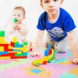 Little girl and boy are building a house out of blocks — Stock Photo