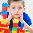 Royalty-Free Stock Photo: The little boy builds a house out of blocks