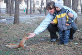 Boy with mother feeds a squirrel — Stock Photo
