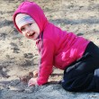 The little girl fell to the sand, and is on her knees — Stock Photo