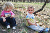 Menino e menina sentada em uma floresta — Foto Stock