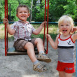 The girl shakes her boy on a swing — Stock Photo #25428527