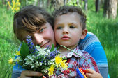 Dziewczyna i chłopak z bukietem kwiatów dzikiego — Zdjęcie stockowe