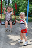 The girl shakes her boy on a swing — Stock Photo