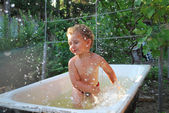 In rural areas,outdoors,little boy bathes in the bath, indulge i — Stock Photo