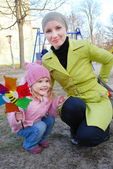 Girl with mother playing with windmill — Stock Photo