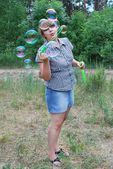 Girl in the woods blowing soap bubbles — Stock Photo