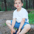 In a pine forest, a little serious boy is sitting in the stump — Stock Photo