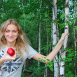 In birch forest, a beautiful girl eats an apple. — Stockfoto