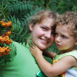 In the woods near a tree with rowan, mother holds her son in he — Stock Photo