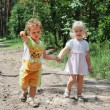 In the forest along the road are a little boy and girl holding — Stock Photo