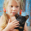 A small village sad girl holding a dog — Stock Photo