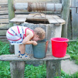 in the village near the well a little boy drinks water from a b — Stock Photo
