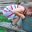 In the village near the well a little boy drinks water from a b — Stock Photo #27452269