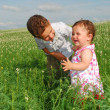 In the field of flowers is a brother and keeps the little siste — Stock Photo