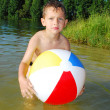 the lake a little boy playing with an inflatable ball — Stock Photo