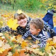 Stock Photo: In forest, mother lies on grass and hugging her son, th