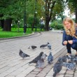 the park, the girl feeding pigeons — Stock Photo