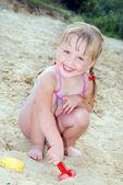 на пляже неподалеку от озера в песок маленькая девочка, играя с — Стоковое фото