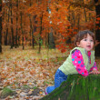 In the forest little girl playing near the stump. — Stockfoto