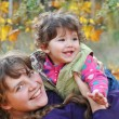 Mom plays with her daughter, dabbles in the autumn forest — Stock Photo