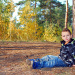 forest little boy sits near a pine — Stock Photo