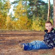 Forest little boy sits near a pine — Stock Photo #33555263