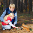 In the pine forest father and daughter feed a squirrel nuts. — Stock Photo