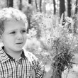 Upset little boy with a bouquet of flowers — Stockfoto