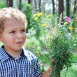 Upset little boy with a bouquet of flowers — Stock Photo